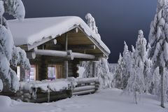 Christmas house. Wooden cottage in the forest covered by snow Stock Photo