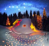 Christmas House in the Carpathians. Mountain shelter is a refuge for tourists and hunters in the winter with a fire fire in the middle of the high mountain of stock image