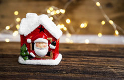 Christmas house decoration with Santa and festive lights on wood Stock Photo
