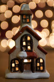 Christmas House Ornament. Cute little Christmas House ornament with glowing tealight inside.  Fairy lights in the background Royalty Free Stock Image