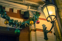 Christmas house outdoor decorations and lantern. Balls and lights on fir Stock Photography