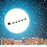 Christmas house in snowfall at the night. Happy holiday greeting card with town skyline. Flying Santa Claus and deer black silhouettes, snow and big moon Stock Images