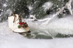 Christmas Ice Skates. A pair of miniature ice skates with evergreen and bell decoration on ice covered pond, snow covered branches and evergreens in snowy Royalty Free Stock Photo