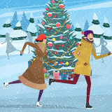 Christmas on ice skating rink. Couple skating near Christmas tree on ice skating rink - Christmastime concept Stock Image