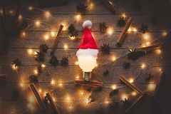 Christmas illuminations and bulb in Santa Claus hat. Cinnamon with star anise around on wooden background. Image in old color style Stock Photo