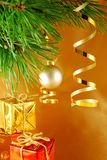 Christmas image. Branch of christmas tree with gold ribbon and gifts under stock photography