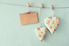 Christmas image of fabric hearts and empty card for adding text hanging on rope in front of blue wooden background. retro filtered Royalty Free Stock Image