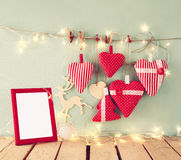 Christmas image of fabric red hearts and blank frame, garland lights, hanging on rope in front of blue wooden background Stock Image