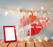 Christmas image of fabric red hearts and blank frame, garland lights, hanging on rope in front of blue wooden background Royalty Free Stock Photos