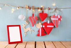Christmas image of fabric red hearts and blank frame, garland lights, hanging on rope in front of blue wooden background Stock Photos