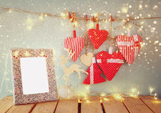 Christmas image of fabric red hearts and blank frame, garland lights, hanging on rope in front of blue wooden background Stock Images