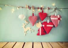 Christmas image of fabric red hearts and garland lights, hanging on rope in front of blue wooden background. retro filtered. Royalty Free Stock Images