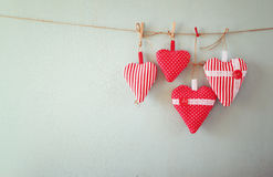 Christmas image of fabric red hearts hanging on rope in front of wooden background. retro filtered Royalty Free Stock Image