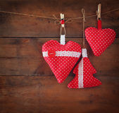 Christmas image of fabric red hearts and tree hanging on rope in front of wooden background. retro filtered Royalty Free Stock Photos