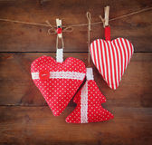Christmas image of fabric red hearts and tree hanging on rope in front of wooden background. retro filtered Stock Images