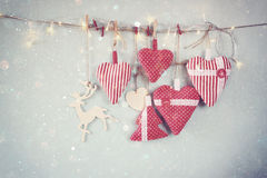 Christmas image of fabric red hearts and tree. wooden reindeer and garland lights, hanging on rope Royalty Free Stock Photos
