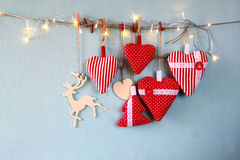 Christmas image of fabric red hearts and tree. wooden reindeer and garland lights, hanging on rope Royalty Free Stock Photography