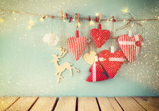 Christmas image of fabric red hearts and tree. wooden reindeer and garland lights, hanging on rope. In front of blue wooden background. retro filtered Royalty Free Stock Photo