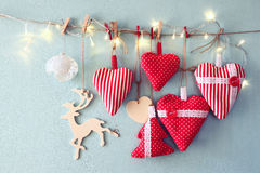 Christmas image of fabric red hearts and tree. wooden reindeer and garland lights, hanging on rope Royalty Free Stock Images