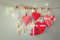 Christmas image of fabric red hearts and tree. wooden reindeer and garland lights, hanging on rope Stock Photography
