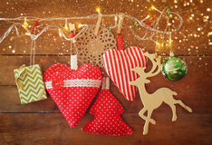 Christmas image of fabric red hearts and tree. wooden reindeer and garland lights, hanging on rope in front of blue wooden backgro Royalty Free Stock Image