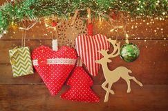 Christmas image of fabric red hearts and tree. wooden reindeer and garland lights, hanging on rope in front of wooden background Stock Photos