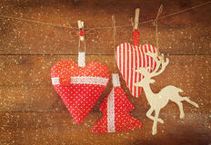 Christmas image of fabric red hearts and tree. wooden reindeer and garland lights, hanging on rope in front of wooden background. Stock Photo