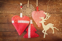 Christmas image of fabric red hearts and tree. wooden reindeer and garland lights, hanging on rope in front of wooden background. Royalty Free Stock Photos