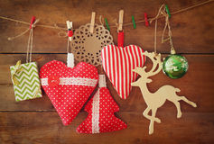Christmas image of fabric red hearts and tree. wooden reindeer and garland lights, hanging on rope in front of wooden background Stock Images