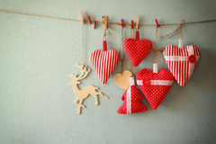 Christmas image of fabric red hearts and tree, wooden reindeer, hanging on rope in front of blue wooden background. retro filtered Royalty Free Stock Photo
