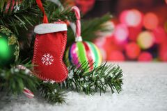 Christmas photography picture of tree branches and red stocking with candy canes and red fairy lights in background. Christmas image of soft material red Royalty Free Stock Photos