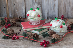 Christmas image of two bowls of vanilla ice-cream adorned by pine cones and cranberries Royalty Free Stock Photography