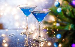 Christmas image of two wine glasses with blue cocktail and garland Stock Photography