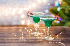 Christmas image of two wine glasses with green cocktail, caramel sticks Royalty Free Stock Photo
