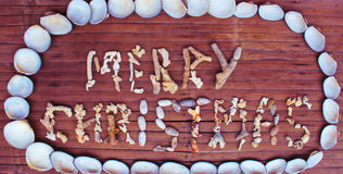 Christmas inscription from white corals and shells on wooden background. stock photo