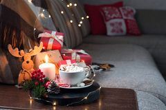 Christmas interior with a Cup of Coffee on the sofa, gift boxes, garlands and Christmas composition royalty free stock images