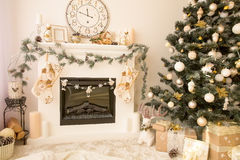 Christmas interior with fireplace and xmas tree. Christmas decorated house interior with fireplace, wall clock, xmas tree and presents under it. Merry xmas and Royalty Free Stock Images