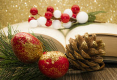 Christmas items with book. Red decorations with open book and golden background Royalty Free Stock Images