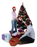 Christmas joy. Studio shot of a young men giving a gift to his girlfriend in front of the Christmas Tree, against a white background Royalty Free Stock Images