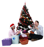 Christmas joy. Studio shot of a young couple enjoying the gifts in front of the Christmas Tree, against a white background Royalty Free Stock Photography