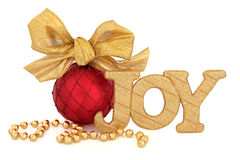 Christmas Joy. Golden glitter sign, red bauble with gold bow and bead chain over white background Royalty Free Stock Images