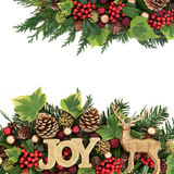 Christmas Joy Abstract Border. Christmas background abstract border with joy glitter sign, reindeer ornament, red and gold bauble decorations, holly, ivy, pine Royalty Free Stock Images