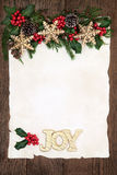 Christmas Joy. Christmas background border with gold joy sign and snowflake bauble decorations, holly, ivy and winter greenery on parchment paper over old oak Stock Images