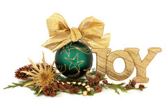 Christmas Joy Decoration. Christmas joy sign with green bauble decoration, gold thistle flower, bead strand, cedar leaf sprigs and pine cones over white Stock Images