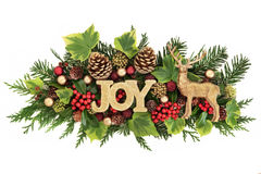 Christmas Joy Decoration. Christmas decoration with joy glitter sign, reindeer ornament, red and gold bauble decorations, holly, ivy, pine cones and fir leaf Stock Images
