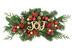 Christmas Joy Decoration. Christmas decoration with gold glitter joy sign, bauble decorations, holly, ivy, snow covered pine cones, cedar cypress and fir leaf Royalty Free Stock Images