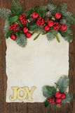 Christmas Joy Decorative Border. Christmas abstract background border with gold glitter joy sign, holly, ivy, mistletoe and snow covered fir on parchment paper Royalty Free Stock Image