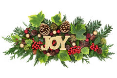 Christmas Joy Decorative Display. Christmas decorative display with joy glitter sign, red and gold bauble decorations, holly, ivy, pine cones and fir leaf sprigs Royalty Free Stock Photography