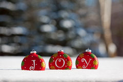 Christmas Joy. Holiday ornaments spell out JOY as these colorful decorations sit in snow on a sunny day. Snow covered pine trees create a background with room Royalty Free Stock Photos