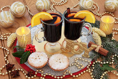 Christmas Joy Scene. Christmas still life scene with gold glitter joy sign, mulled wine, mince pies, gold bauble decorations, candles, fruit and spices, holly Royalty Free Stock Photography